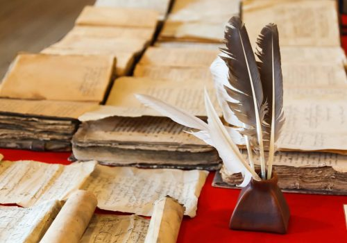 feathers and inkpot with Old books on the red tablecloth